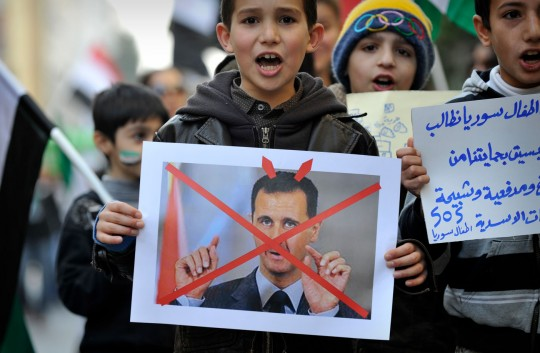 Syrian children living in Athens take part in a demonstration against Syrian President Bashar al-Assad in Athens on March 15, 2012, marking  the first anniversary of the anti-regime revolt. AFP PHOTO / LOUISA GOULIAMAKI (Photo credit should read LOUISA GOULIAMAKI/AFP/Getty Images)
