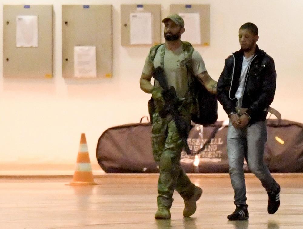 Suposto terrorista é escoltado por policial federal no aeroporto de Brasilia, em 12 de julho de 2016. Autoridades brasileiras prenderam 10 membros de uma suposta organização terrorista que atacaria durante os Jogos Olímpicos.