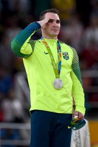 RIO DE JANEIRO, BRAZIL - AUGUST 15:  Silver medalist Arthur Zanetti of Brazil salutes during the national anthem on the podium at the medal ceremony for Men's Rings on day 10 of the Rio 2016 Olympic Games at Rio Olympic Arena on August 15, 2016 in Rio de Janeiro, Brazil.  (Photo by Laurence Griffiths/Getty Images)