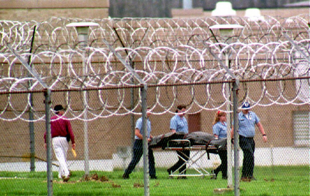 LUCASVILLE, OH - APRIL 15:  Paramedics remove the body of a prison guard held hostage at the Southern Ohio Correctional Facility 15 April, 1993. The guard died while being held by rioting inmates. No reason was given for his death. The prisoners continue to hold eight guards in a cellblock of the facility.  (Photo credit should read EUGENE GARCIA/AFP/Getty Images)