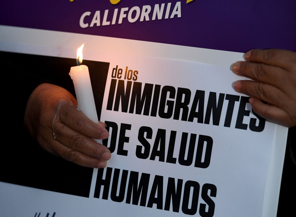 """Migrant rights groups hold candles during a vigil to protest against US President Donald Trump's new crackdown on """"sanctuary cities"""", outside the City Hall in Los Angeles on January 25, 2017.Some 300 such cities, counties or states -- from New York to Los Angeles -- exist throughout the United States, and many of them have vowed since Trump's election to protect the estimated 11 million undocumented migrants living in the country. / AFP / Mark RALSTON (Photo credit should read MARK RALSTON/AFP/Getty Images)"""