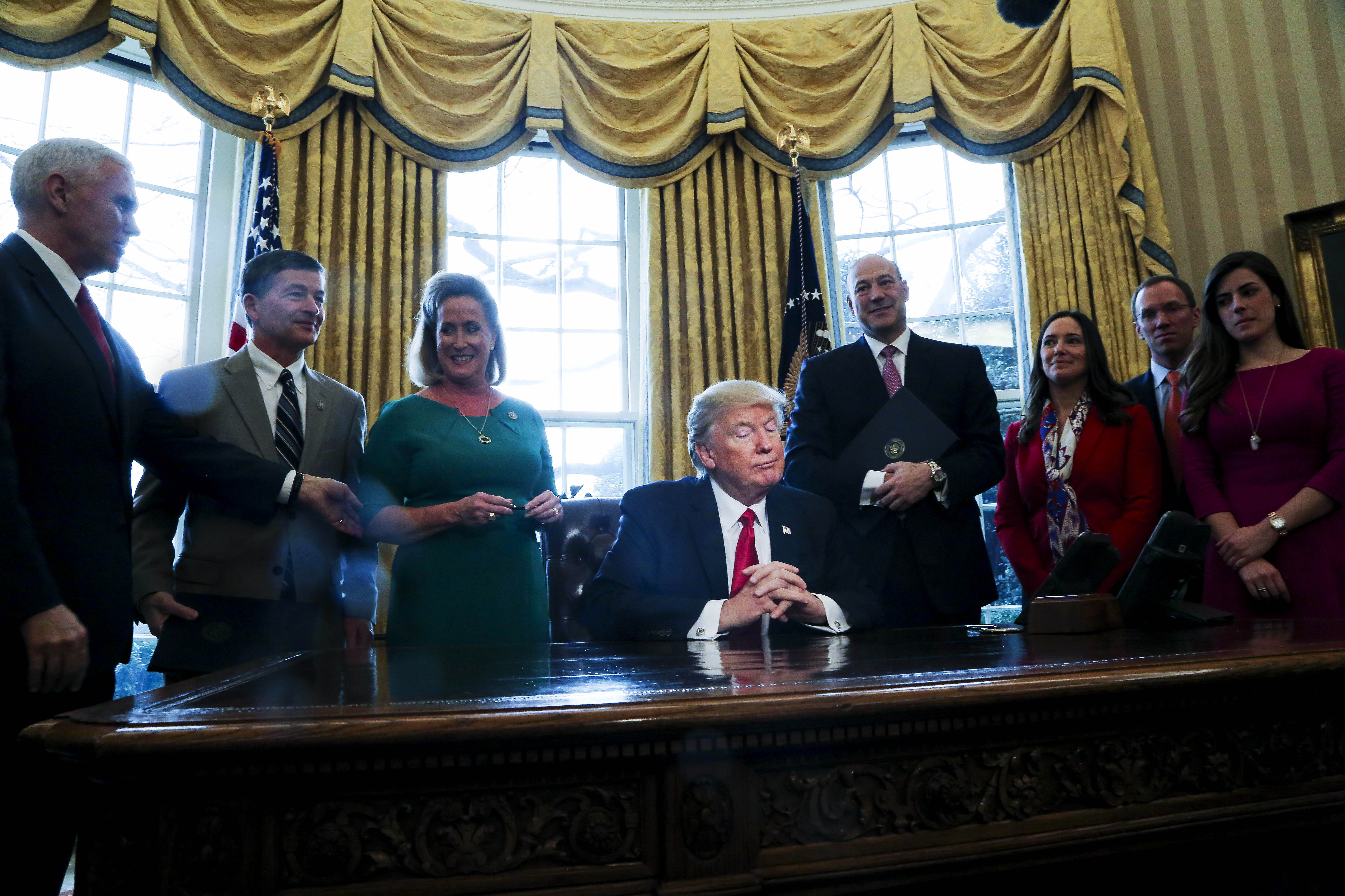 WASHINGTON, DC - FEBRUARY 3: (AFP OUT) U.S. President Donald Trump pauses as he signs Executive Orders in the Oval Office of the White House, including an order to review the Dodd-Frank Wall Street to roll back financial regulations of the Obama era February 3, 2017 in Washington, DC. (Photo by Aude Guerrucci - Pool/Getty Images)