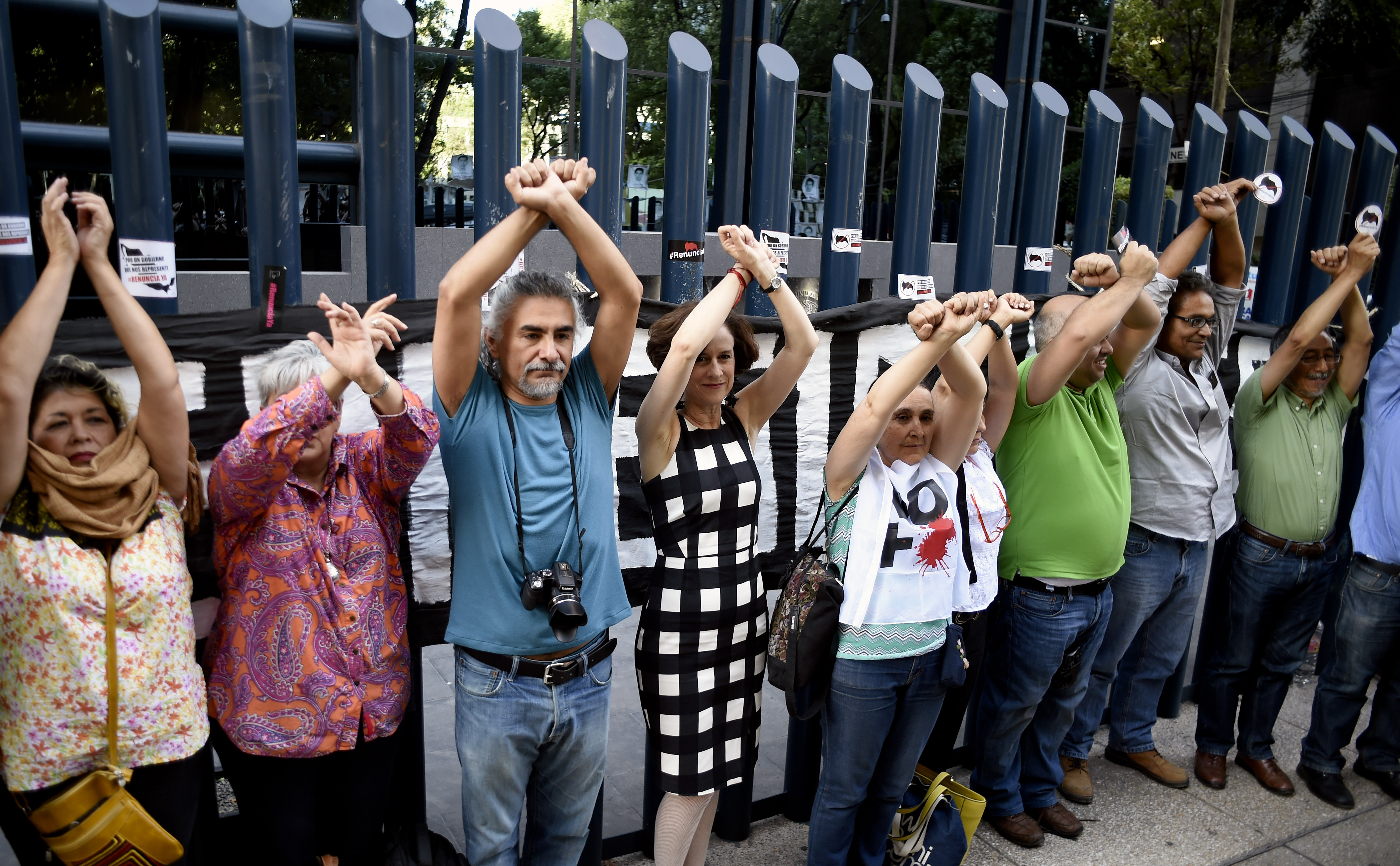 Civil society activists and journalists pretend to turn themselves in during a protest against alleged government spying on the media and human rights defenders, outside the attorney general's office in Mexico City on June 23, 2017. Mexican prosecutors said Wednesday they have opened an investigation into allegations the government spied on leading journalists, human rights activists and anti-corruption campaigners. / AFP PHOTO / ALFREDO ESTRELLA (Photo credit should read ALFREDO ESTRELLA/AFP/Getty Images)