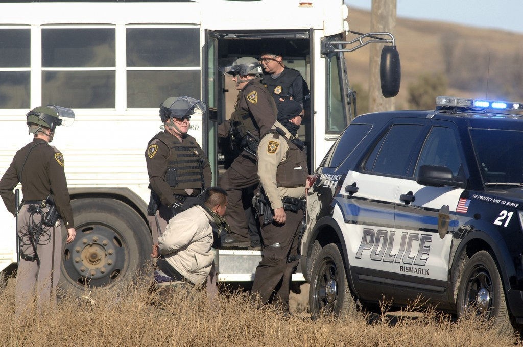 A Dakota Access Pipeline protester is arrested and waiting transportation to the Morton County jail on Tuesday, Nov. 15, 2016, after a large gathering of protesters tried to block a railroad crossing on Old Highway 10 and County Road 82 west of Mandan, N.D. (Mike McCleary /The Bismarck Tribune via AP)