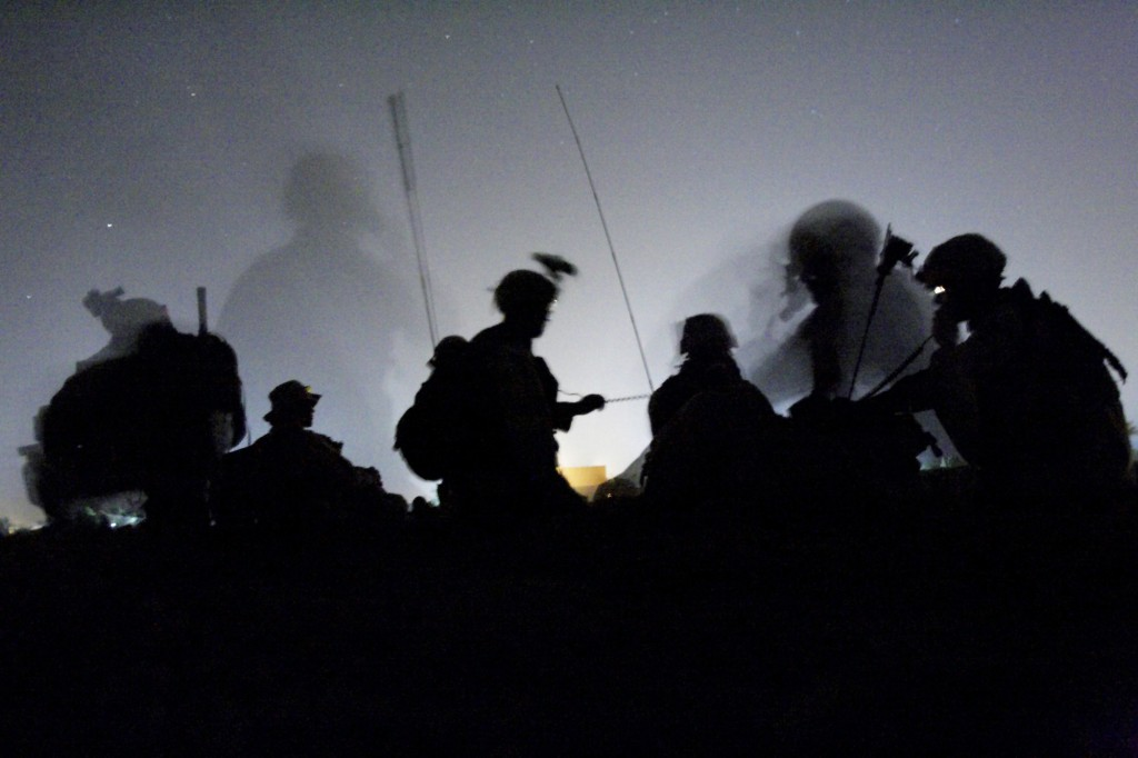 U.S. Army soldiers make radio contact after arriving by helicopter at night at an undisclosed location south of Baghdad, Iraq where they believed a top leader of the insurgency and close associated of Abu Musab al-Zarqawi was hiding, Sunday, June 5, 2005. Although the insurgent leader was not found, Americans and soldiers from the Iraqi Intervention Force detained 15 people. (AP Photo/Jacob Silberberg)