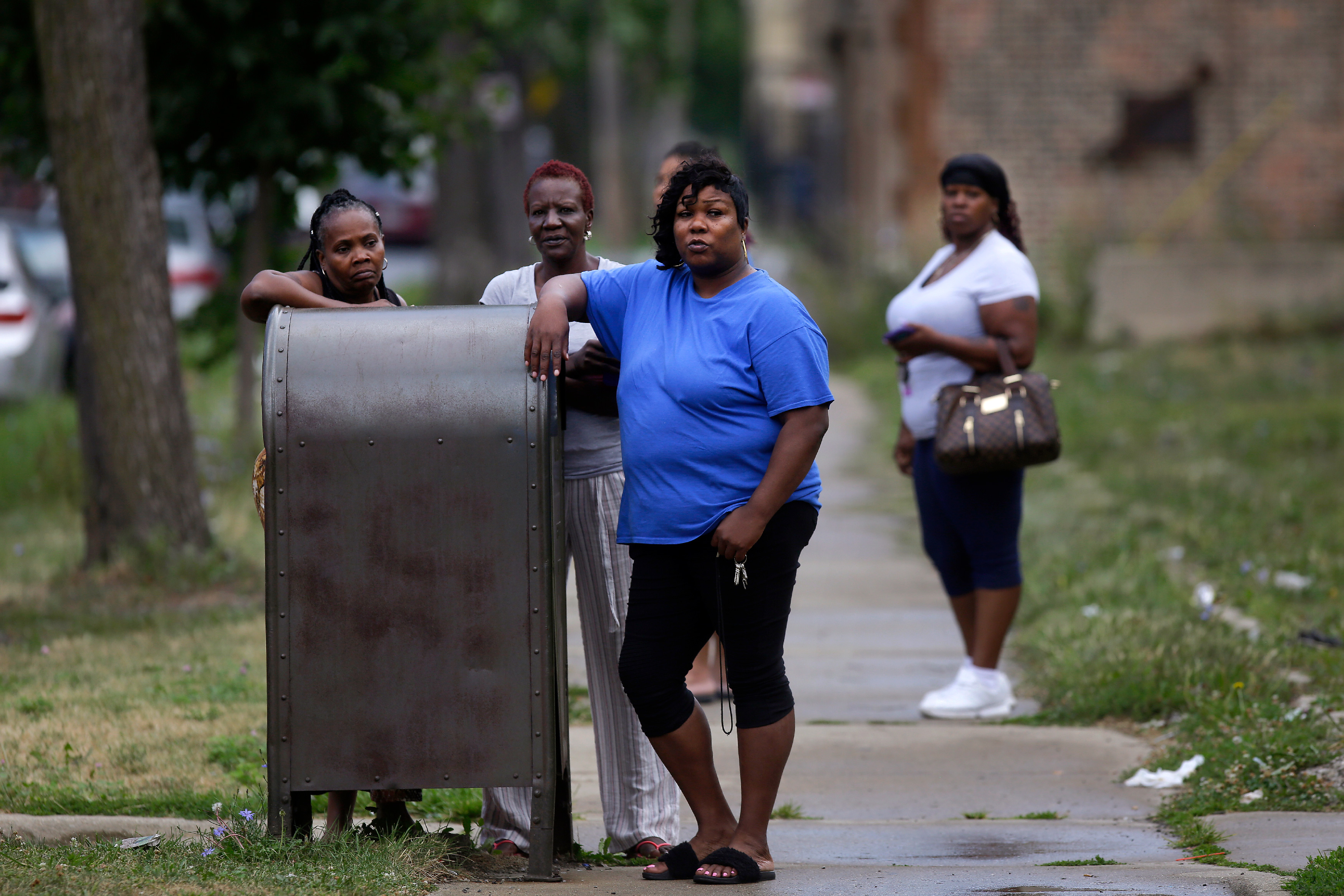 Bystanders watch as Chicago Police officers and detectives investigate a shooting where multiple people were shot on Sunday, August 5, 2018 in Chicago, Illinois. In the last 24 hours over 30 people have been shot and at least 2 killed across Chicago including five mass shootings, where four or more victims were shot at one location. (Photo by Joshua Lott/Getty Images)