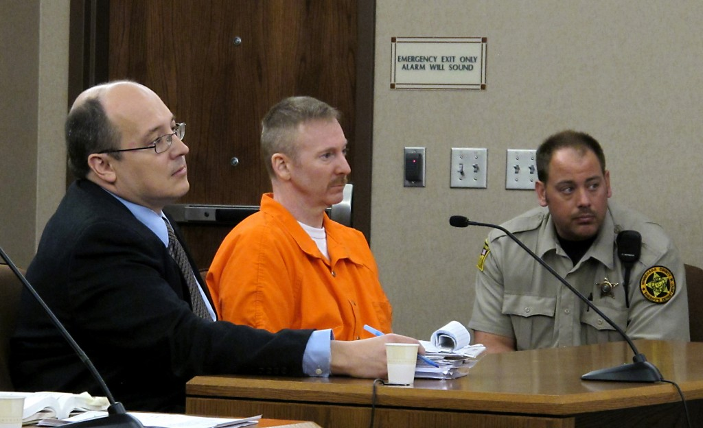 """Eric Robert, center, and his defense lawyer, Mark Kadi, listen to Judge Brad Zell read the sentence for Robert's killing senior corrections officer Ronald """"R.J."""" Johnson during a failed escape attempt in Sioux Falls, S.D., Thursday, Oct. 27, 2011. Robert was given the death penalty. (AP Photo/Argus Leader, Devin Wagner)"""