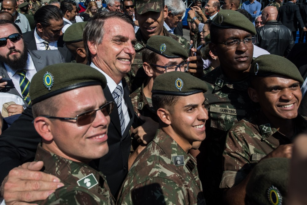 Brazilian congressman and presidential canditate for the next election, Jair Bolsonaro (L), takes pictures with militaries during an military event in Sao Paulo, Brazil on May 3, 2018. (Photo by Nelson ALMEIDA / AFP) (Photo credit should read NELSON ALMEIDA/AFP/Getty Images)