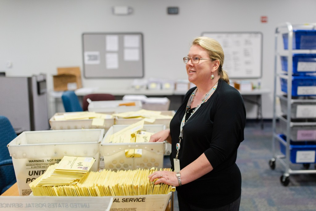 Lynn Ledford, director of voter registration and elections for Gwinnett County (Ga.), stands over absentee ballots that have been mailed in while talking to a reporter at the Gwinnett County Voter Registrations and Elections Office in Lawrenceville, Ga., on Wednesday, Oct. 17, 2018. Photo by Kevin D. Liles for The Intercept
