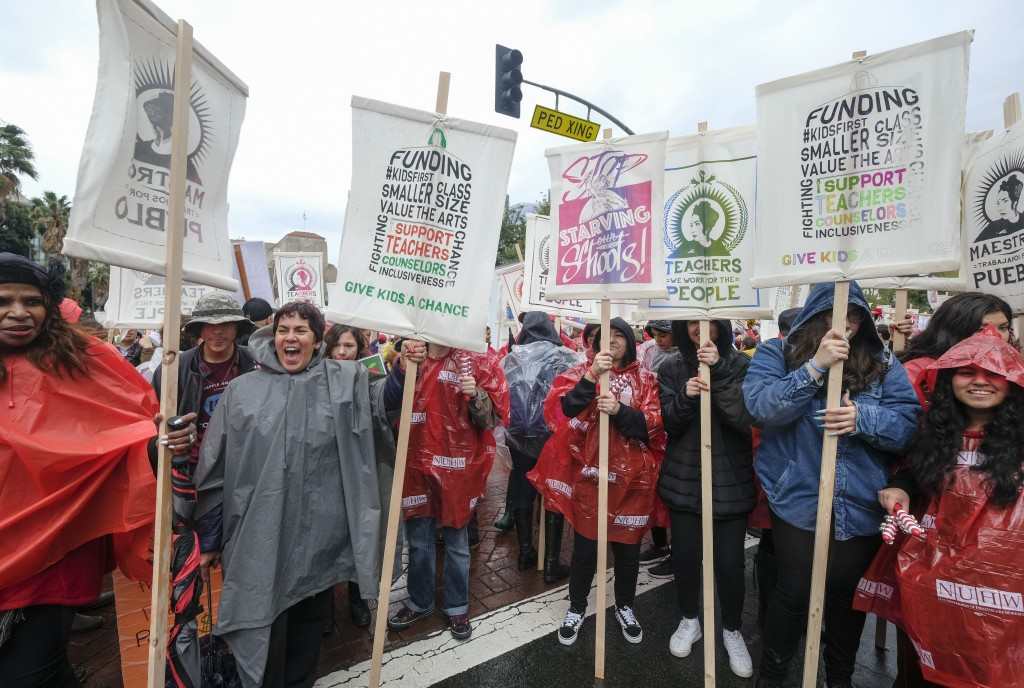 Teachers and supporters hold signs and umbrellas in the rain during a rally Monday, Jan. 14, 2019, in Los Angeles. Tens of thousands of Los Angeles teachers went on strike Monday for the first time in three decades after contract negotiations failed in the nation's second-largest school district, but schools stayed open with the help of substitutes and district officials said students were learning. (AP Photo/Ringo H.W. Chiu)