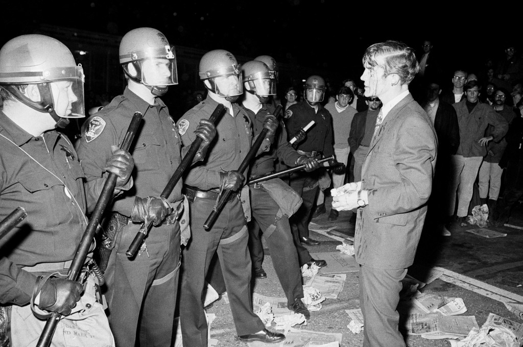 (Original Caption) 5/22/1968-San Francisco, CA- Attorney Terence Hallinan, his face bloody from a gash in his head, confronts the police officer he claims laid his head open while he was trying to help a girl to safety, away from the police. The incident took place after police arrested some 27 demonstrators who were conducting a sit-in in the Administration Building at San Francisco State College late 5/21.