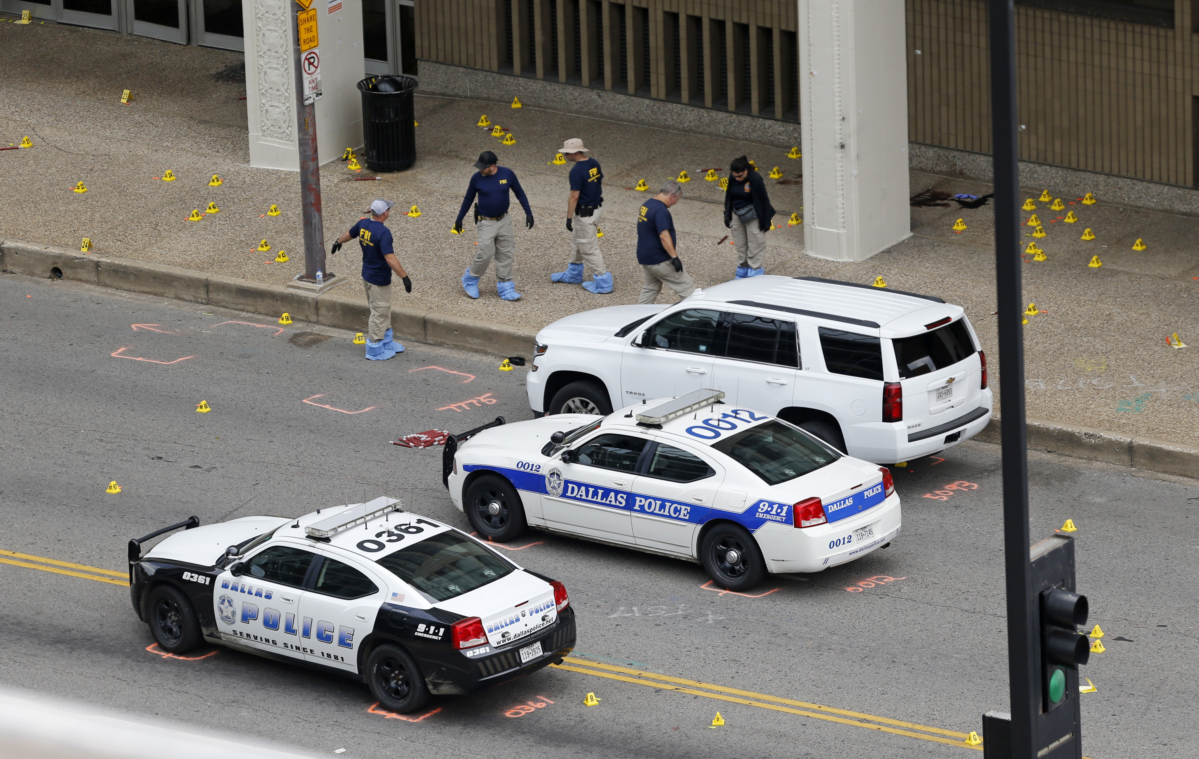Members of an FBI evidence response team work at the scene of the attack on police officers in Dallas, Saturday, July 9, 2016. A peaceful protest over the recent videotaped shootings of black men by police turned violent Thursday night as gunman Micah Johnson fatally shot several officers. (AP Photo/Gerald Herbert)