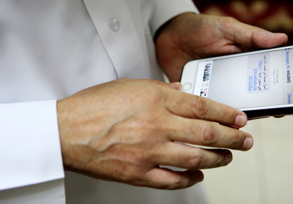 """Human rights activist Ahmed Mansoor shows Associated Press journalists a screenshot of a spoof text message he received in Ajman, United Arab Emirates, on Thursday, Aug. 25, 2016. Mansoor was recently targeted by spyware that can hack into Apple's iPhone handset. The company said Thursday it has updated its security. The text message reads: """"New secrets on the torture of Emirati citizens in jail."""" (AP Photo/Jon Gambrell)"""