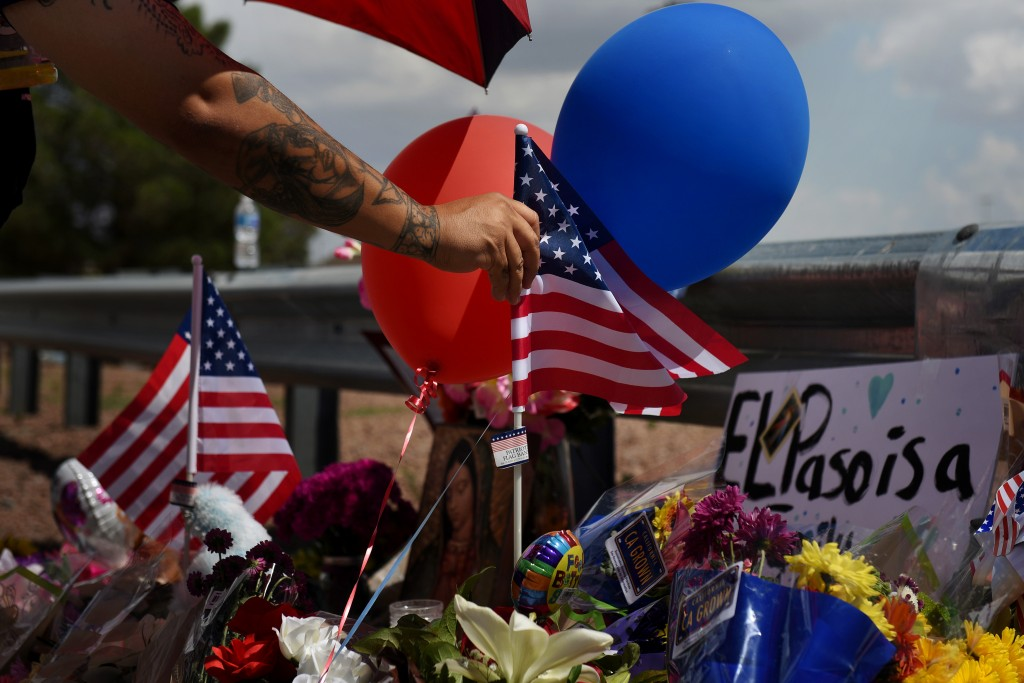 A man places an American flag in the pile of flowers that has gathered a day after a mass shooting at a Walmart store in El Paso, Texas, U.S. August 4, 2019.