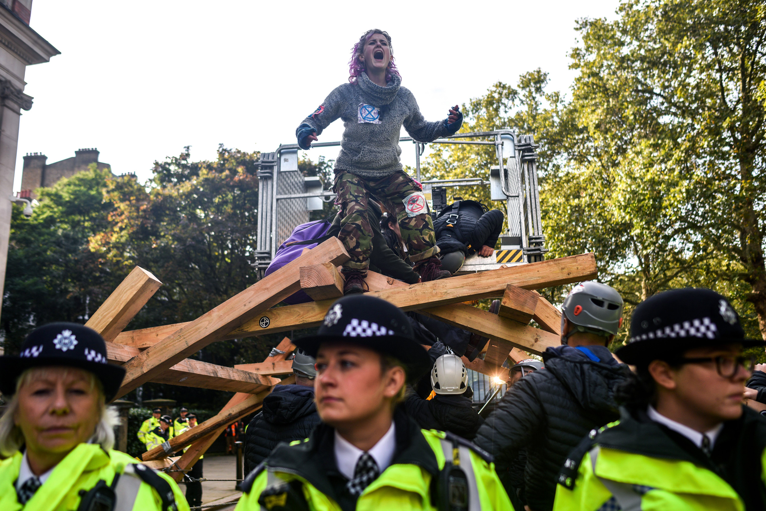LONDON, ENGLAND - OCTOBER 09: Extinction Rebellion activists stand on a wooden platform behind a police line on October 9, 2019 in London, England. Climate change activists are gathering to block access to various government departments as they launch a two week protest in central London. (Photo by Peter Summers/Getty Images)