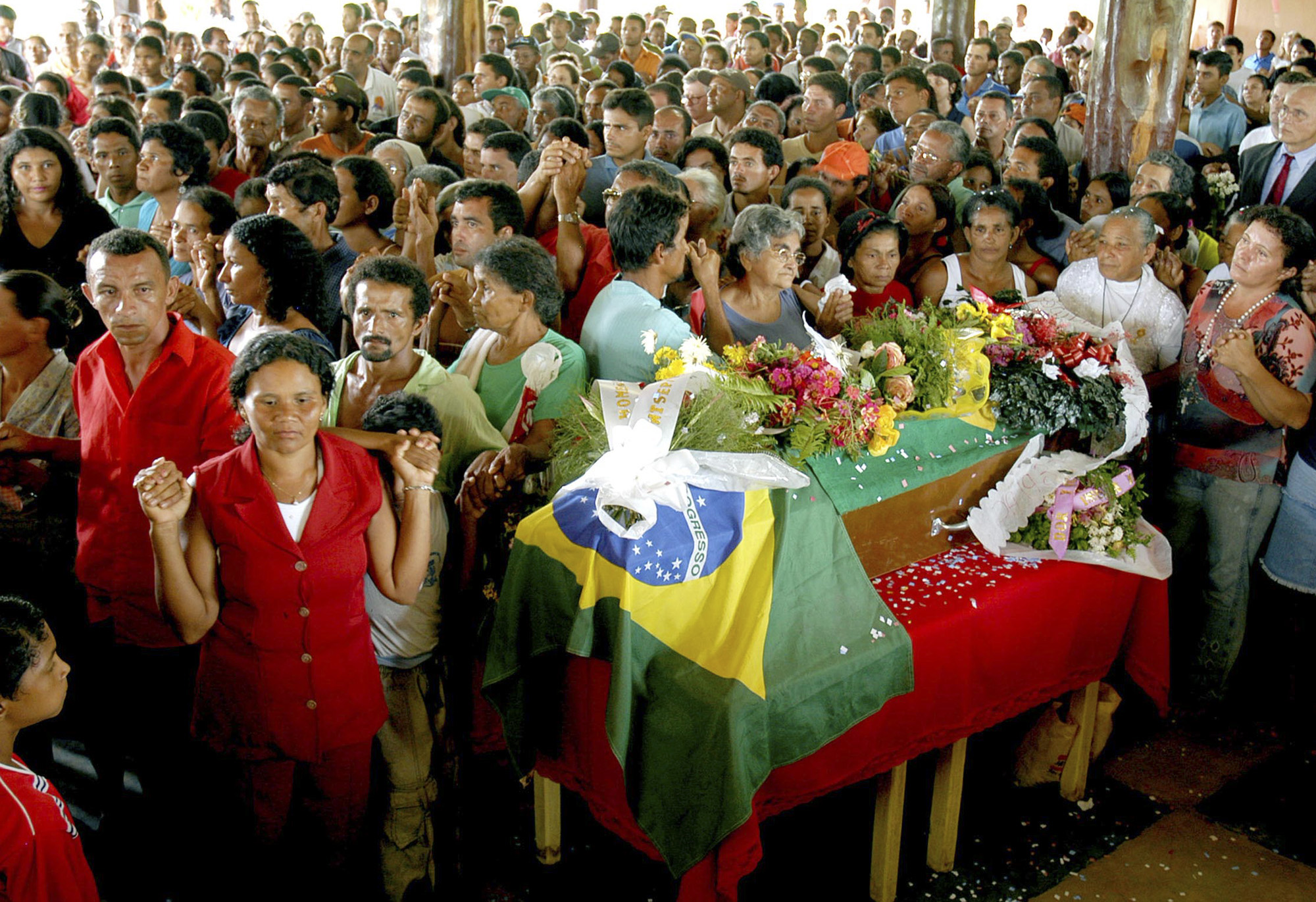People gather during the wake of Dorothy Stang whose casket is drapped in a Brazilian flag in Anapu on Saturday Feb. 15, 2005. Stang, 73, was shot dead on Feb. 12, 2005, in a dispute with an influential rancher in the eastern Amazon state of Para, on the frontier of forest and development, where powerful interests collide with the Amazon's poor. (AP Photo/Paulo Santos) **EFE OUT**