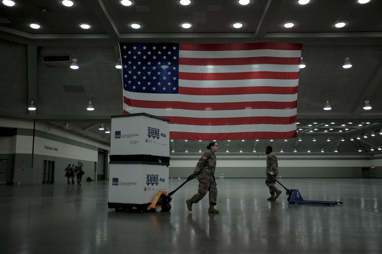 Membros da Guarda Nacional de Maryland descarregam caixas com camas da FEMA, a Agência Nacional de Emergências, no centro de convenções de Baltimore, Maryland, em 28 de março de 2020. A Guarda Nacional montou um hospital de campanha com 250 leitos para pacientes com a covid-19.