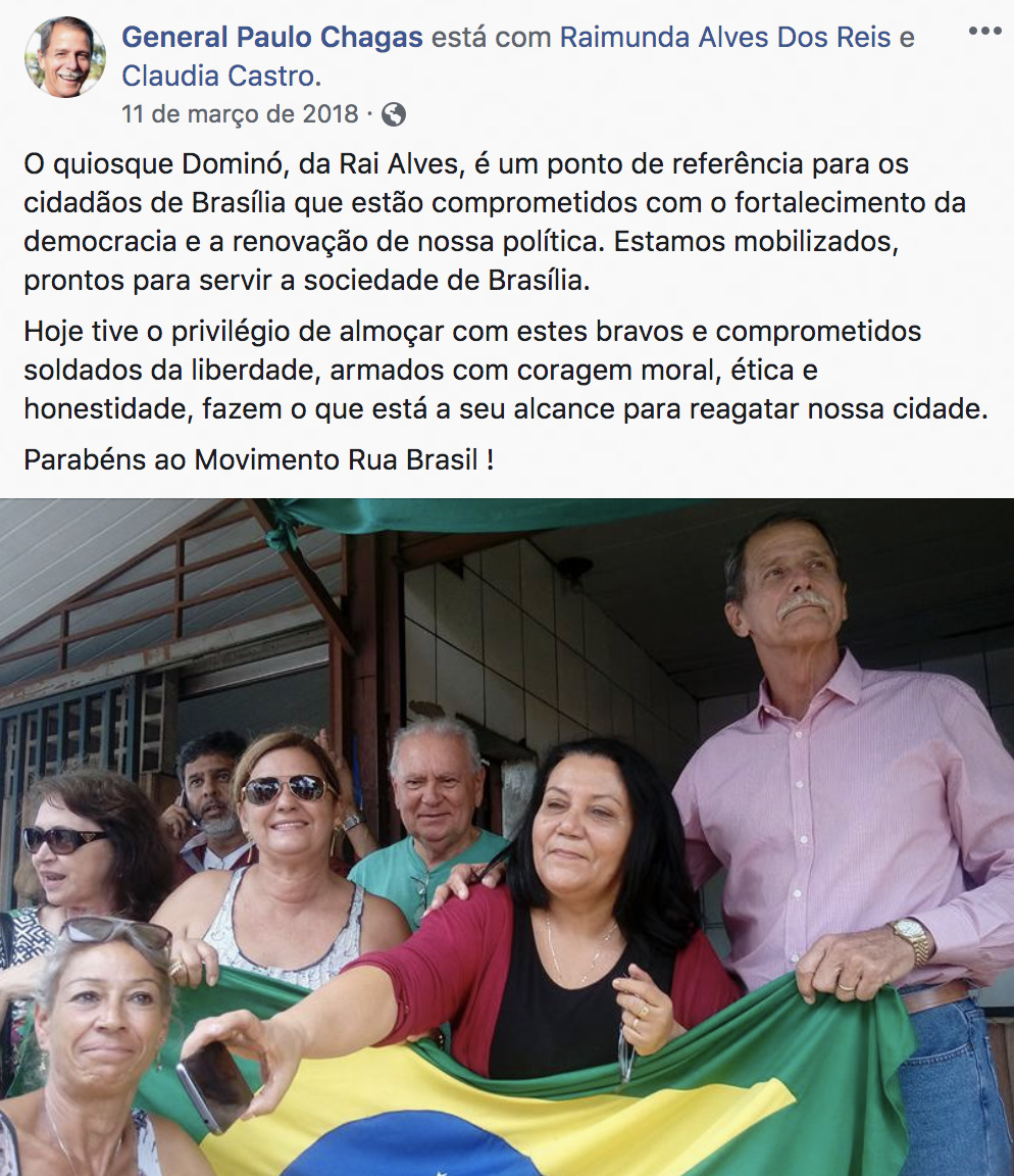 O militar da reserva Paulo Chagas, de camisa rosa ao lado de Reis, segura a bandeira nacional com membros do Movimento Rua Brasil, dirigido pela servidora de Damares.