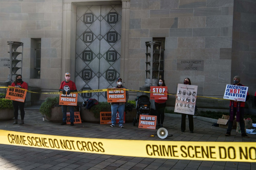 Demonstrators protest federal executions of death row inmates, in front of the US Justice Department in Washington, DC, on December 10, 2020. - US federal authorities have scheduled five executions starting on December 10 through January 15, 2021. Four of the five are Black men; the fifth, Lisa Montgomery, would be the first woman to be executed by the federal government in nearly 70 years. (Photo by Nicholas Kamm / AFP) (Photo by NICHOLAS KAMM/AFP via Getty Images)