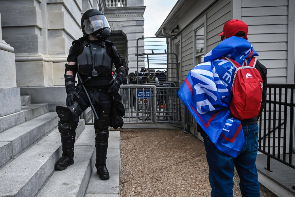 A Trump supporter confronts police and security forces at the US Capitol in Washington, DC, on January 6, 2021. - Demonstrators breeched security and entered the Capitol as Congress debated the a 2020 presidential election Electoral Vote Certification. (Photo by ANDREW CABALLERO-REYNOLDS / AFP) (Photo by ANDREW CABALLERO-REYNOLDS/AFP via Getty Images)