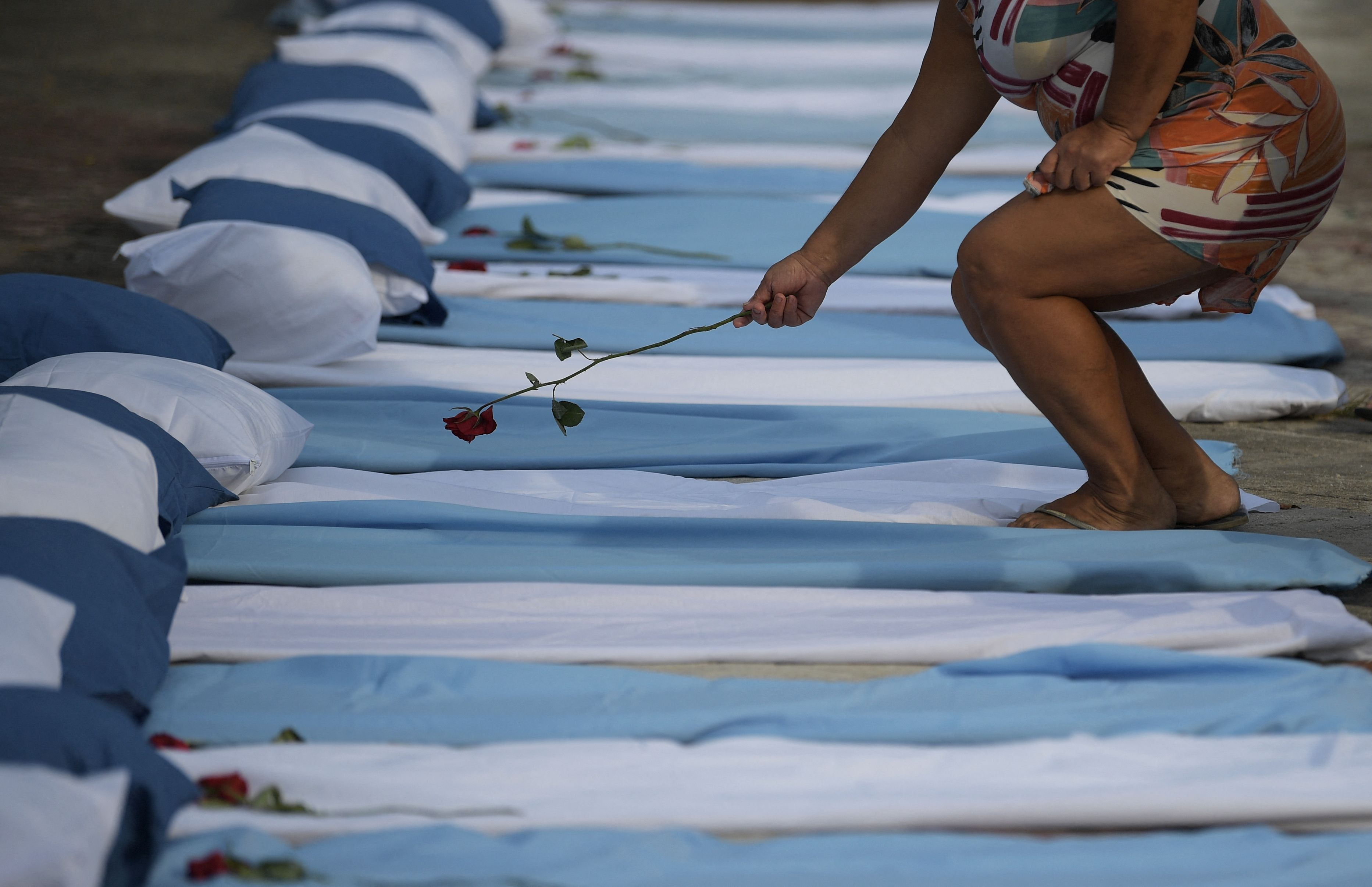 TOPSHOT - A woman lays a rose on top of a mattress symbolizing COVID-19 victims during a protest by the Rio de Paz human rights activist group outside a hospital in Rio de Janeiro, Brazil, on March 24, 2021. - The group were protesting against the rising figures of COVID-19 deaths in the country which saw more than 3000 people die in the last 24 hours. (Photo by CARL DE SOUZA / AFP) (Photo by CARL DE SOUZA/AFP via Getty Images)